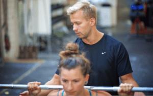 Personlig træner i københavn, Niels' Training hjælper klient med et back squat