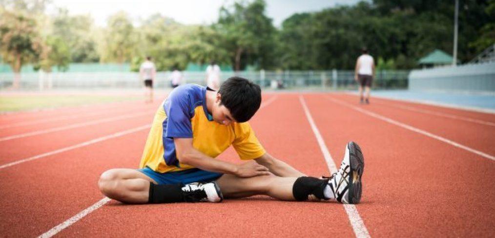 Fodboldspiller laver udstrækningsøvelser til baglår
